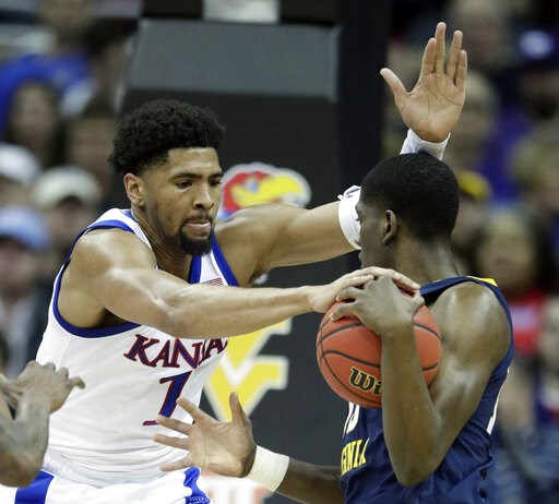 (AP Photo/Orlin Wagner). Kansas forward Dedric Lawson (1) covered West Virginia forward Lamont West, right, during the first half of an NCAA college basketball game in the semifinals of the Big 12 conference tournament in Kansas City, Mo., Friday, Marc...