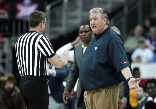 (AP Photo/Charlie Riedel). West Virginia head coach Bob Huggins talks to an official during the first half of an NCAA college basketball game against Kansas in the Big 12 men's tournament Friday, March 15, 2019, in Kansas City, Mo.