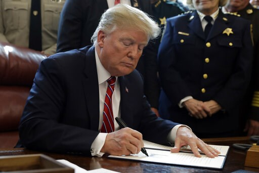 (AP Photo/Evan Vucci). President Donald Trump signs the first veto of his presidency in the Oval Office of the White House, Friday, March 15, 2019, in Washington. Trump issued the first veto, overruling Congress to protect his emergency declaration for...