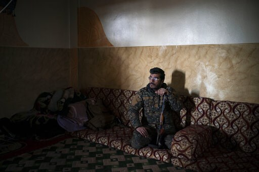 (AP Photo/Felipe Dana). In this Feb. 18, 2019 photo, Dia Hassakeh, 45, a fighter in the Kurdish-led U.S-backed Syrian Democratic Forces, looks out of a building in Baghouz, Syria. Eight years of war have left their mark on Dia. In the early days of the...