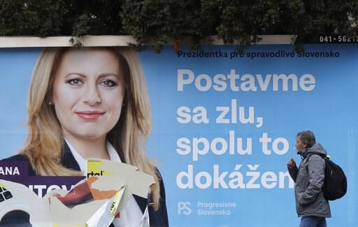 (AP Photo/Petr David Josek). A man walks past a campaign poster for Zuzana Caputova in Bratislava, Slovakia, Friday, March 15, 2019. Caputova is one of the favorite candidates to succeed Slovakia's President Andrej Kiska in the upcoming election. Slova...