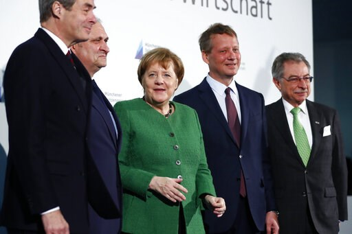 (AP Photo/Matthias Schrader). German Chancellor Angela Merkel, center, poses for a group photo with economy leaders prior to talks about Germany's economy in Munich, Germany, Friday, March 15, 2019.