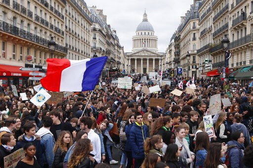 (AP Photo/Francois Mori). High school students demonstrate near the Pantheon monument, seen in background, one carrying the French flag, Friday, March 15, 2019 in Paris. Students worldwide are skipping class Friday to take to the streets to protest the...