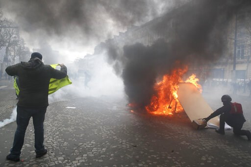 (AP Photo/Christophe Ena). Yellow vests protesters set a burricade afire on the Champs Elysees avenue Saturday, March 16, 2019 in Paris. French yellow vest protesters clashed Saturday with riot police near the Arc de Triomphe as they kicked off their 1...