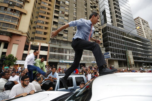 (AP Photo/Eduardo Verdugo). National Assembly President Juan Guaido, who declared himself interim president of Venezuela, leaps on to a vehicle to speak to supporters as he visits different points of anti-government protest in Caracas, Venezuela, on Tu...