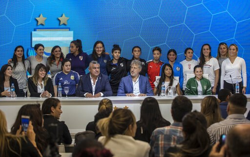 (AP Photo/Daniel Jayo). Accompanied by soccer players, Claudio Tapia, president of Argentina's Soccer Federation, bottom center, and General Secretary of the Argentina's Footballers' Union (FAA) Sergio Marchi, bottom, second from right, pose for pictur...