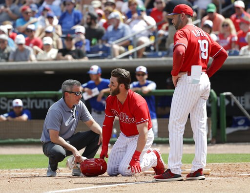 (Yong Kim/The Philadelphia Inquirer via AP). Philadelphia Phillies' Bryce Harper, center, yells toward Toronto Blue Jays pitcher Trent Thornton as manager Gabe Kapler, right, and assistant trainer Chris Mudd check on him after he was hit by a pitch dur...