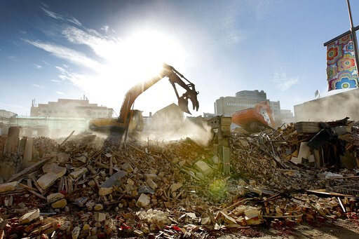 (AP Photo/Martin Hunter, File). FILE- In this photo taken Friday, July 8, 2011, an excavator works on clearing rubble following the Feb. 2011, quake, in downtown Christchurch, New Zealand. Despite its tranquility and beauty, New Zealand city of Christc...