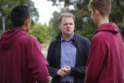 (AP Photo/Vincent Thian). Cashmere High School principal Mark Wilson, center, speaks with his students at the school in Christchurch, New Zealand, Sunday, March 17, 2019. Three students from the high school were at the Al Noor Mosque for Friday prayers...