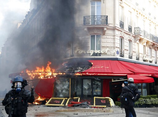 (AP Photo/Christophe Ena). Paris famed restaurant Fouquet's burns on the Champs Elysees avenue during a yellow vests demonstration Saturday, March 16, 2019 in Paris. Paris police say more than 100 people have been arrested amid rioting in the French ca...