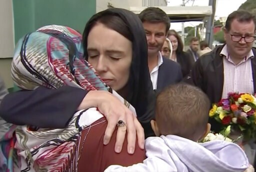 (TVNZ via AP). In this image made from video, New Zealand's Prime Minister Jacinda Ardern, center, hugs and consoles a woman as she visited Kilbirnie Mosque to lay flowers among tributes to Christchurch attack victims, in Wellington, Sunday, March 17, ...