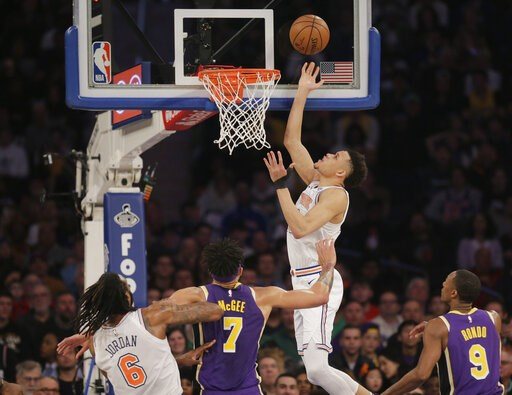 (AP Photo/Seth Wenig). New York Knicks' Kevin Knox, top, scores during the first half of an NBA basketball game against the Los Angeles Lakers, Sunday, March 17, 2019, in New York.