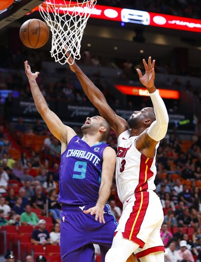 (AP Photo/Wilfredo Lee). Charlotte Hornets guard Tony Parker (9) goes up to shoot against Miami Heat guard Dwyane Wade (3) during the first half of an NBA basketball game, Sunday, March 17, 2019, in Miami.