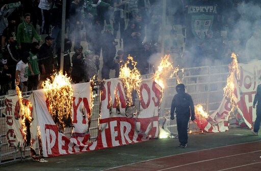 (InTime Sports via AP). Fans burn a banner in front of stands during a Greek Super League soccer match inside the Athens' Olympic stadium, in Athens, Sunday, March 17, 2019. The derby between Greek league archrivals Panathinaikos and Olympiakos has bee...