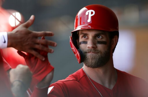(AP Photo/Chris O'Meara). Philadelphia Phillies' Bryce Harper high-fives teammates after being taken out during the third inning of a spring training baseball game against the Toronto Blue Jays, Saturday, March 9, 2019, in Clearwater, Fla.