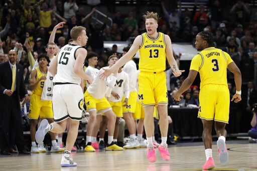 (AP Photo/Nam Y. Huh). Michigan's Ignas Brazdeikis (13) reacts after shooting a 3-point basket during the first half of an NCAA college basketball championship game against Michigan State in the Big Ten Conference tournament, Sunday, March 17, 2019, in...