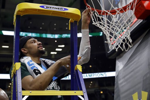 (AP Photo/Nam Y. Huh). Michigan State's Kenny Goins cuts a piece of the net after defeating Michigan 65-60 in an NCAA college basketball championship game in the Big Ten Conference tournament, Sunday, March 17, 2019, in Chicago.