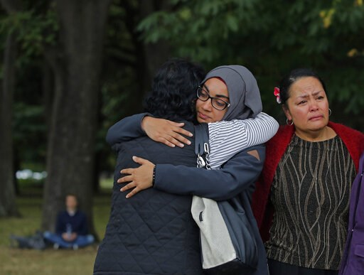 (AP Photo/Vincent Yu). Mourners hug after paying their respects to the victims near the Masjid Al Noor mosque in Christchurch, New Zealand, Monday, March 18, 2019. A steady stream of mourners paid tribute at makeshift memorial to the 50 people slain by...