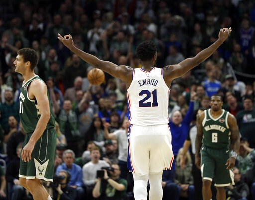 (AP Photo/Aaron Gash). Philadelphia 76ers' Joel Embiid (21) reacts after making a shot during the second half of the team's NBA basketball game against the Milwaukee Bucks on Sunday, March 17, 2019, in Milwaukee. The 76ers won 130-125.