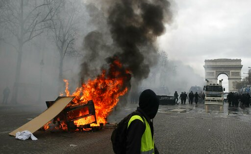 (AP Photo/Christophe Ena). A barricade burns on the Champs Elysees avenue Saturday, March 16, 2019 in Paris. French yellow vest protesters clashed Saturday with riot police near the Arc de Triomphe as they kicked off their 18th straight weekend of demo...