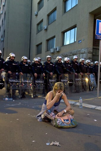 (AP Photo/Marko Drobnjakovic). A woman sits in front of a riot police cordon after a standoff in Belgrade, Serbia, Sunday, March 17, 2019. Supporters of the Serbian opposition clashed with police on Saturday and Sunday in Belgrade, the capital, were th...