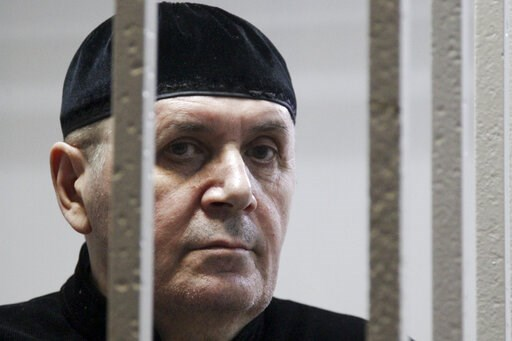 (AP Photo/Musa Sadulayev). Oyub Titiev, the head of a Chechnya branch of the prominent human rights group Memorial, stands behind bars in court before a hearing in Shali, Russia, Monday, March 18, 2019. Oyub Titiyev was detained in January 2018 and cha...