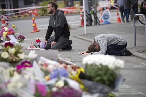 (AP Photo/Vincent Thian). Mourners pray near the Linwood mosque in Christchurch, New Zealand, Tuesday, March 19, 2019. Christchurch was beginning to return to a semblance of normalcy Tuesday. Streets near the hospital that had been closed for four days...