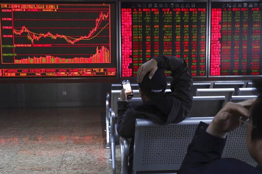 (AP Photo/Ng Han Guan). An investor plays a mobile chess game while watching stock prices at a brokerage in Beijing, China, Tuesday, March 19, 2019. Asian shares were mixed in muted trading Tuesday as investors awaited the U.S. Federal Reserve meeting ...