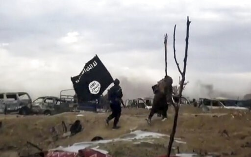 (Aamaq News Agency via AP). This frame grab from video posted online Monday, March 18, 2019, by the Aamaq News Agency, a media arm of the Islamic State group, shows IS fighters walking as they hold the group's flag inside Baghouz, the Islamic State gro...