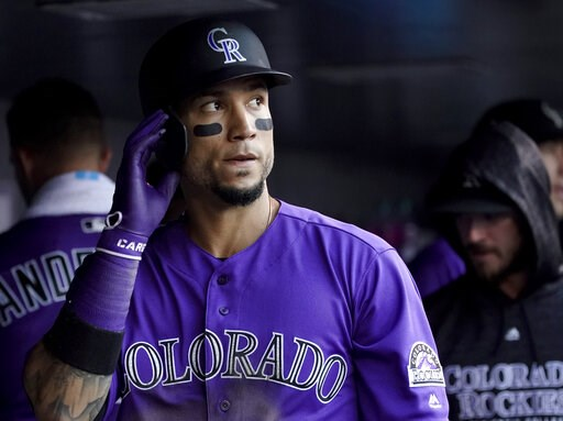 (AP Photo/Jack Dempsey, File). FILE - In this June 18, 2018, file photoColorado Rockies' Carlos Gonzalez walks in the dugout after scoring against the New York Mets during the second inning of a baseball game in Denver. A person familiar with the agree...