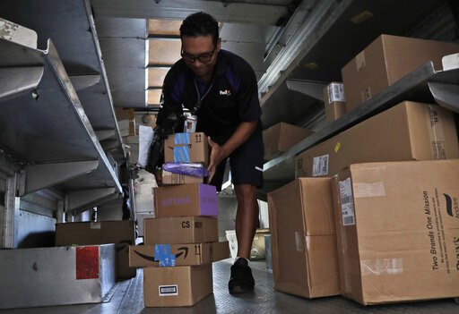 (AP Photo/Lynne Sladky, File). FILE- In this July 17, 2018, file photo, a FedEx employee delivers packages in Miami. FedEx reports financial results on Tuesday, March 19, 2019.