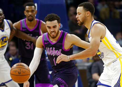 (AP Photo/Jim Mone). Minnesota Timberwolves' Tyus Jones, left, and Golden State Warriors' Stephen Curry chase the loose ball in the first half of an NBA basketball game Tuesday, March 19, 2019, in Minneapolis.