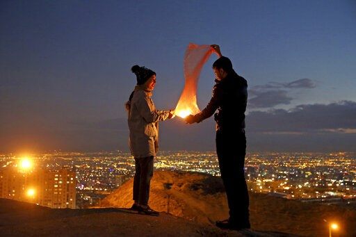 "(AP Photo/Ebrahim Noroozi). A couple lights a lantern during a celebration, known as ""Chaharshanbe Souri,"" or Wednesday Feast, marking the eve of the last Wednesday of the solar Persian year, Tuesday, March 19, 2019, in Tehran, Iran. Iran's many woes b..."