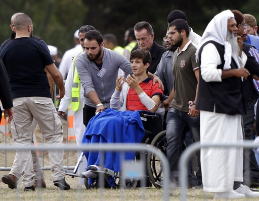 (AP Photo/Mark Baker). Zaed Mustafa, in wheelchair, brother of Hamza and son of Khalid Mustafa killed in the Friday March 15 mosque shootings reacts during the burial at the Memorial Park Cemetery in Christchurch, New Zealand, Wednesday, March 20, 2019.