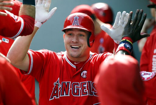 (AP Photo/Ted S. Warren, File). FILE - In this Sept. 10, 2017, file photo, Los Angeles Angels' Mike Trout is greeted in the dugout after hitting a solo home run in the first inning of a baseball game against the Seattle Mariners in Seattle. A person fa...