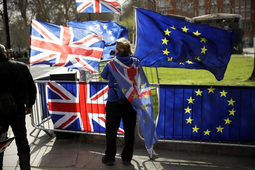 (AP Photo/Matt Dunham). An anti-Brexit supporter stands by European and British Union flags placed opposite the Houses of Parliament in London, Monday, March 18, 2019. British Prime Minister Theresa May was making a last-minute push Monday to win suppo...