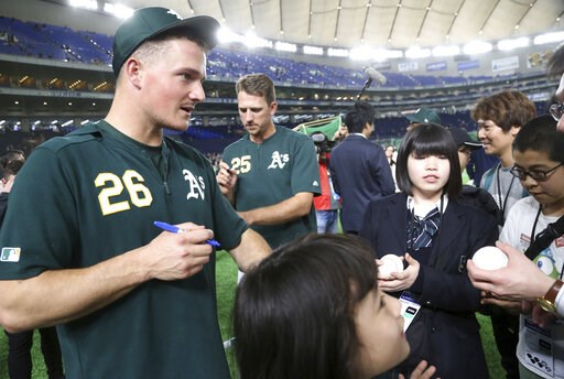 (AP Photo/Koji Sasahara). Oakland Athletics third baseman Matt Chapman (26) gives his autographs to fans prior to Game 1 of a Major League opening series baseball game between the Seattle Mariners and the Athletics at Tokyo Dome in Tokyo, Wednesday, Ma...