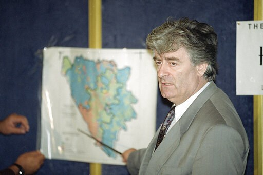(AP Photo/Denis Paquin, File). FILE - In this Aug. 25, 1992 file photo, Radovan Karadzic, Bosnian Serb leader in Bosnia-Herzegovina, indicates the Serb territories in Yugoslavia during a news conference in London. Nearly a quarter of a century since Bo...