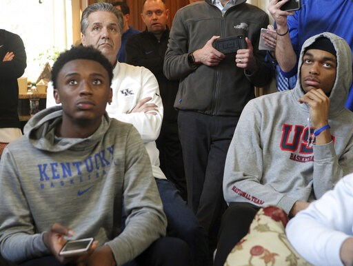 (AP Photo/James Crisp). Kentucky's Ashton Hagans, coach John Calipari, left rear, and PJ Washington, right, watch the broadcast of the NCAA men's Division I college basketball tournament selection show at Calipari's home in Lexington, Ky., Sunday, Marc...