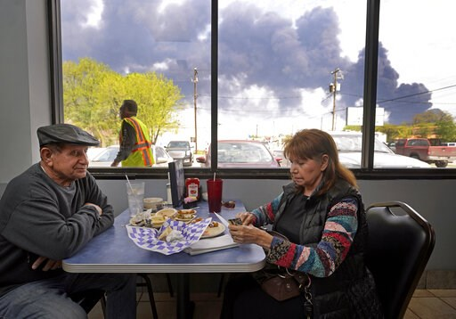 (Melissa Phillip/Houston Chronicle via AP). Charlie Tamez and his wife, Dalia Tamez, finish their lunch at Ken's Restaurant, 1122 Center St., as the chemical fire at Intercontinental Terminals Company continues to send dark smoke over Deer Park, Texas,...