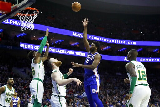 (AP Photo/Matt Slocum). Philadelphia 76ers' Joel Embiid (21) shoots as Boston Celtics' Terry Rozier, from right, Aron Baynes, Marcus Smart and Al Horford watch during the first half of an NBA basketball game, Wednesday, March 20, 2019, in Philadelphia.