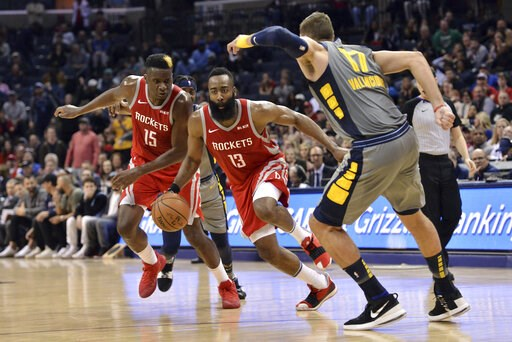 (AP Photo/Brandon Dill). Houston Rockets guard James Harden (13) drives between teammate Clint Capela (15) and Memphis Grizzlies center Jonas Valanciunas (17) during the second half of an NBA basketball game Wednesday, March 20, 2019, in Memphis, Tenn....