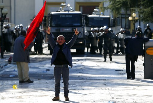 (AP Photo/Visar Kryeziu). A protester flashes the victory sign as thousands of opposition supporters protest in Tirana, Albania on Saturday, March 16, 2019. Albanian opposition supporters clashed with police while trying to storm the parliament buildin...