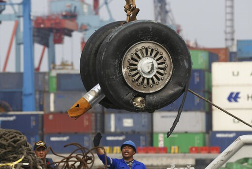 (AP Photo/Achmad Ibrahim, File). FILE - In this Saturday, Nov. 3, 2018, file photo, a crane moves a pair of wheels recovered from the Lion Air jet that crashed into the Java Sea for further investigation at Tanjung Priok Port in Jakarta, Indonesia.  In...