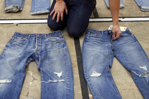 (AP Photo/Jeff Chiu, File). FILE- In this Feb. 9, 2018 photo Bart Sights, head of the Eureka Lab, compares the markings and damage on jeans that he guesses are close to 30 years old, left, to jeans made within a few hours of this photograph at Levi's i...