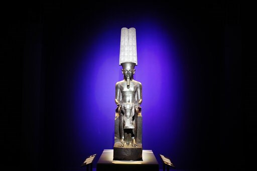 """(AP Photo/Francois Mori). A status of """"The god Amun protecting Tutankhamuns"""" is displayed as part of 'Tutankhamun, the treasure of the Pharaoh', an exhibition in partnership with the Grand Egyptian Museum at the Grande Halle of La Villette in Paris, Fr..."""