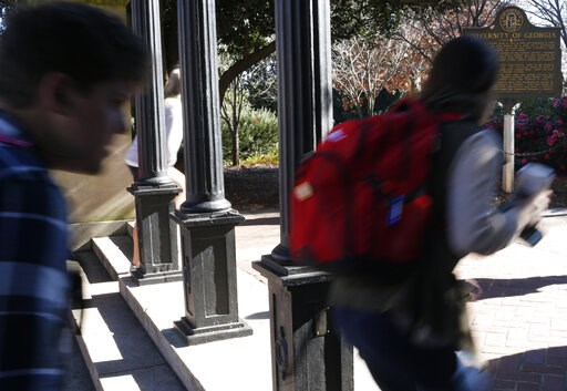 (Joshua L. Jones/Athens Banner-Herald via AP). FILE- In this Jan. 9, 2019, file photo University of Georgia undergraduate students avoid walking under the university arch on the first day of the spring semester in Athens, Ga. At orientation every UGA s...