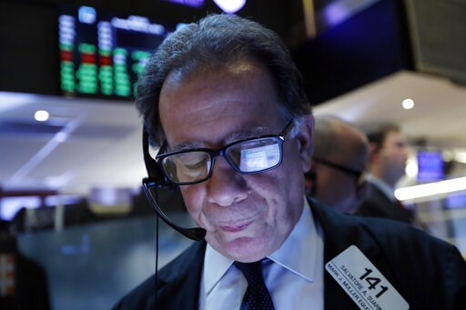 (AP Photo/Richard Drew, File). FILE- In this March 12, 2019, file photo a handheld device of trader Sal Suarino is reflected in his glasses as he works on the floor of the New York Stock Exchange. The U.S. stock market opens at 9:30 a.m. EDT on Thursda...