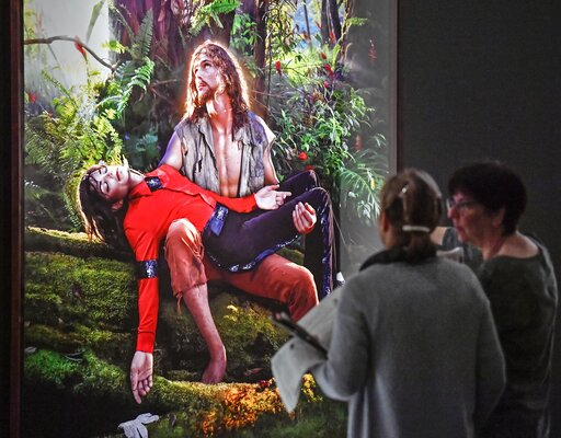 (AP Photo/Martin Meissner). Visitors talk about the picture 'American Jesus: Hold me, carry me boldly' from US artist David LaChapelle at a preview of the exhibition 'Michael Jackson: On The Wall' at the Bundeskunsthalle museum in Bonn, Germany, Thursd...