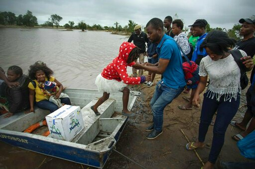 (Josh Estey/CARE via AP). A young girl is helped from a boat after being evacuated from flood waters following cyclone force winds and heavy rain near the coastal city of Beira, Mozambique, Wednesday March 20, 2019. Torrential rains were expected to co...